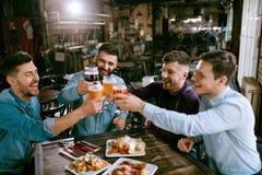 Män som dricker öl i bar royaltyfri bild