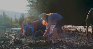 Män som förbereder lägereld nära flodstranden 4k lager videofilmer