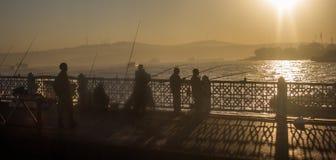 Män som fiskar från den Galata bron Istanbul Turkiet Arkivbild
