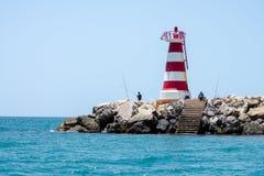Män som fiskar nära en fyr på den Algarve kusten, Portugal Fotografering för Bildbyråer