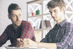 Män som i regeringsställning gör skrivbordsarbete Royaltyfria Foton