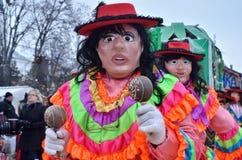 Män som kläs som mexikansk kvinnadans och spelas maraca på traditionellt Pereberia hjälpmedels kläders för ändring carniva, Ukrai arkivfoton