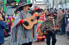 Män som kläs som mexikanska musiker i ponchoar och sombrero som spelar gitarrer på traditionellt Pereberia hjälpmedels kläders fö royaltyfri bild