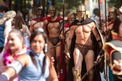Män som kläs som Spartan Warriors Walk In Dragon, lurar ståtar Royaltyfri Fotografi
