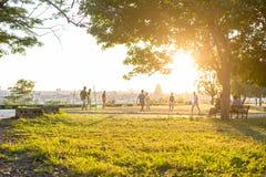 Män som konturer spelar fotboll i, parkerar på soluppgång royaltyfri foto
