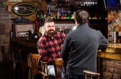 Män som kopplar av i bar Helgfritid fredag avkoppling i bar Vänner som kopplar av i bar Vänlig konversation med arkivbild