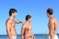 Män som kopplar av på stranden royaltyfri fotografi