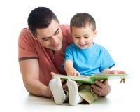 Män som läser en bok till sonen Royaltyfria Bilder