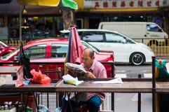 Män som läser tidningen i en gatamarknad Arkivbild