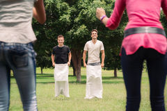 Män som leker säcken, race med flickvänner glädjande Royaltyfri Foto