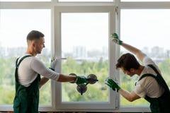 Män som monterar ett fönsteravsnitt arkivbilder
