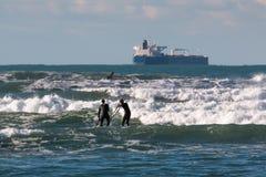 Män som ombord paddleboarding i vågorna, tillförselskepp i backgro arkivfoton