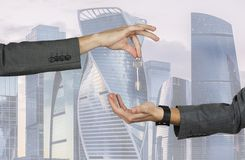 Män som räcker över tangenterna till huset, lägenhet, bil på bakgrunden av byggnader av skyskrapor royaltyfri bild