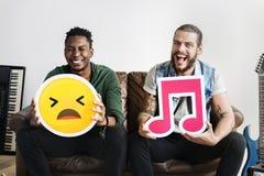 Män som rymmer emoticon- och musiksymboler arkivbilder