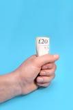 Män som rymmer 20 pund gömma i handflatan in, på blå bakgrund Royaltyfri Fotografi