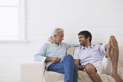 Män som samtalar på Sofa At Home royaltyfri foto