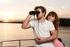 Män som ser in i binocularus, medan hans flicka kramar honom arkivbilder