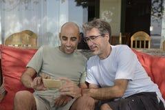 Män som ser på mobiltelefonen Fotografering för Bildbyråer