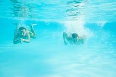 män som simmar två under vatten Arkivbild