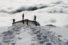 Män som skyfflar snö Arkivfoto