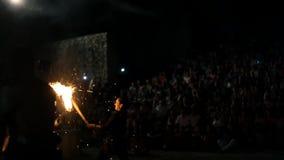 Män som slåss med facklor och spottar brand