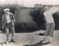Män som spelar golf i trädgård Royaltyfria Bilder