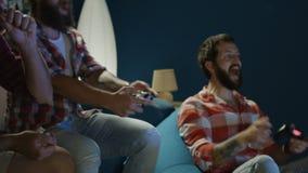 Män som spelar med hemmastadda gamepads stock video