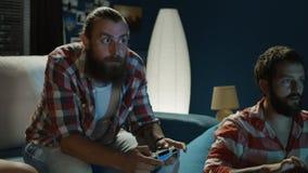Män som spelar med hemmastadda gamepads lager videofilmer