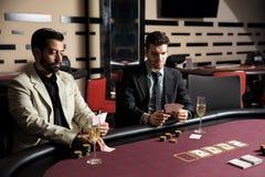 Män som spelar poker på en kasino royaltyfria foton
