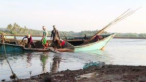 Män som tömmer det sjunkande fartyget på kust i Goa stock video