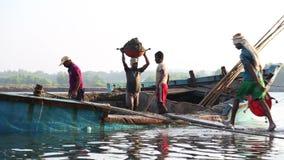 Män som tömmer det sjunkande fartyget på kust i Goa lager videofilmer