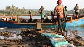 Män som tar sand ut ur ett sjunkande fartyg i Goa lager videofilmer