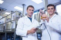 Män som testar produkten och ler på kameran Fotografering för Bildbyråer