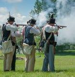 Män som tillsammans avfyrar vapen Royaltyfri Foto