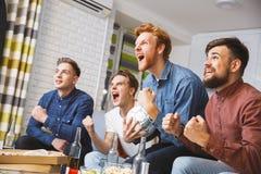 Män som tillsammans håller ögonen på sporten på att ropa för tv som hemma är lyckligt royaltyfri fotografi