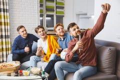 Män som tillsammans håller ögonen på sporten på hemmastadda selfiebilder för tv royaltyfri bild