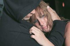 Män som tröstar kvinnan och försöker att lugna ner Arkivbild