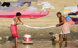 Män som tvättar kläder på ghatsna av Varanasi Royaltyfri Bild