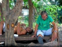 Män som vilar och kopplar av under skuggan av ett träd Arkivbilder