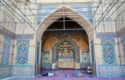 Män sover under kupolen och de färgrika mönstrade väggarna med tegelplattor inom moskén Royaltyfri Fotografi