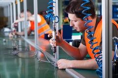 Män under precisionarbete på produktionslinje arkivfoto