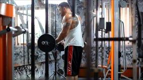 Männen i klubba upp den tunga utrustningen för bodybuilding och honom har starka händer arkivfilmer