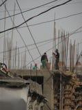 Männer arbeiten an einem Gebäude in Baku, Aserbaidschan mit den enormen hervorstehenden Eisenstangen Stockfoto