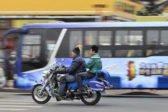 Männer auf chinesischem Motorrad im beschäftigten Verkehr, Dalian, China Lizenzfreies Stockbild