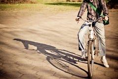 Männer auf fallendem Schatten des Fahrrades Stockbild