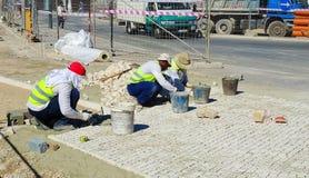 Männer bei der Arbeit - Kubiksteinmontage Stockfotos
