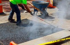 Männer bei der Arbeit, Stadtstraße im Bau, Asphaltierung laufend Stockbild