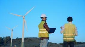 Männer benutzen moderne Geräte nahe Windmühlen, hintere Ansicht stock video footage
