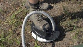 Männer, das Gummiboot über Fußpumpe auf einer Bank des Sees pumpt Er trägt die Militärstiefel stock video footage