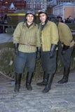 Männer in den durchdachten Militäruniformen werfen für Fotos mit Besuchern der Ausstellung auf Stockbilder